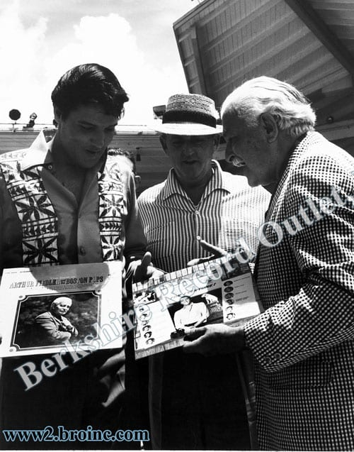 Elvis Presley and Arthur Fiedler exchanging record albums